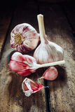 Two whole garlic bulbs beside cloves. On old wooden table for theme about pungent herbs for cooking and health Royalty Free Stock Image