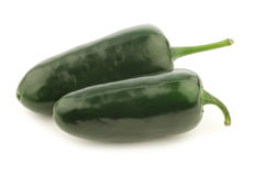 Two whole green jalapeno peppers Royalty Free Stock Images