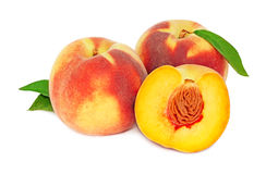 Two whole and a half peaches with green leaves (isolated) Royalty Free Stock Photos
