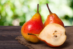 Two whole and half of pear on a wooden table with cloth burlap Stock Images