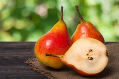 Two whole and half of pear on a wooden table with cloth burlap Royalty Free Stock Photography