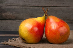Two whole and half of pear on a wooden table with cloth burlap Stock Photography