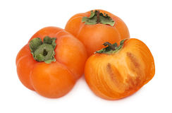 Two whole and a half of ripe persimmon with green leaves (isolat Stock Image