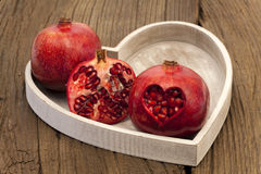 Two whole and one half pomegranate Royalty Free Stock Photos