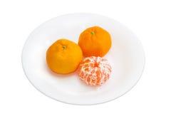 Two whole and one peeled mandarin orange on a white dish Stock Image