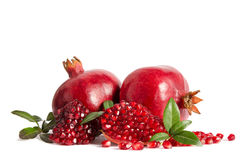 Two whole and part of a pomegranate with pomegranate seeds Stock Photos