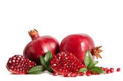 Two whole and part of a pomegranate with pomegranate seeds Stock Images
