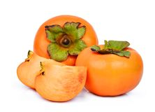 Two whole and slice of fresh ripe persimmons isolated on white Royalty Free Stock Image