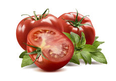 Two whole tomatoes, half and basil leaves  Stock Images