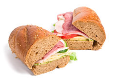 Two whole wheat baguette sandwiches. Two halves of long whole wheat baguette sandwich with lettuce, tomatoes, ham, turkey breast and cheese Royalty Free Stock Photo