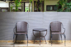 Two wicker chair near wall create a natural feel. Royalty Free Stock Images