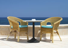 Two wicker chairs on the background of the sea Stock Images