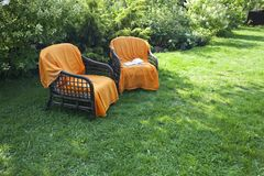 Two wicker chairs in the garden. Two wicker chairs in the beautiful, sunny garden royalty free stock image