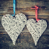Two wicker hearts hanging on old wooden wall. Stock Image