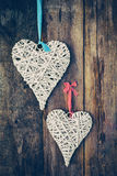 Two wicker hearts hanging on old wooden wall. Royalty Free Stock Photography