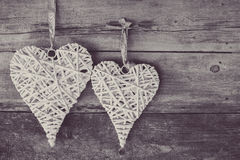 Two wicker hearts hanging on wooden background. Stock Image