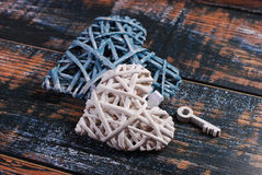 Two wicker hearts and a key on shabby background Royalty Free Stock Photography