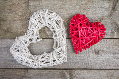 Two wicker hearts on old rustic wooden background. Love, romance, wedding Stock Photos