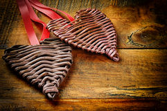 Two wicker hearts on  wooden table Stock Image