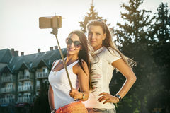Two wild young women taking a selfie. Two wild young women taking a selfi with selfie stick in the street Stock Images