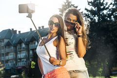 Two wild young women taking a selfie. Two wild young women taking a selfi with selfie stick in the street Stock Photos