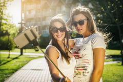 Two wild young women taking a selfie. With selfie stick in the street Stock Photos