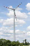 Two wind energy engines against clouds Stock Photos
