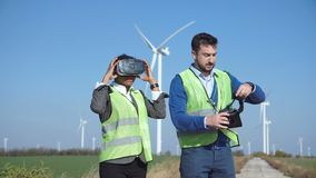 Two wind farm engineers in virtual reality googles. Two engineers in vests standing and gesturing as they put on virtual reality headsets and looking around with stock footage