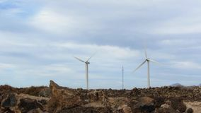 Two Wind Generators on Rocky Ground. With Stones and Bright Cloudy Sky stock video