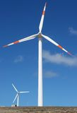 Two wind mill power generators. Against blue sky Stock Images