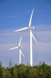 Two wind power generators. Two white wind power generator working under blue sky Stock Photography