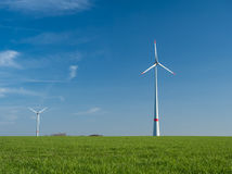 Two wind power plants on a green meadow Royalty Free Stock Photo