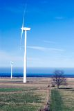 Two wind turbines. Two wind turbine generators in a dry winter or early spring landscape with a blue sky Royalty Free Stock Photography