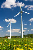 Two wind turbines. Windmills against blue sky with white clouds and yellow flowers on the ground stock photos