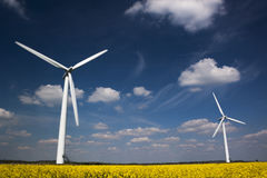 Two Wind Turbines against a blue, cloud-strewn sky Stock Images