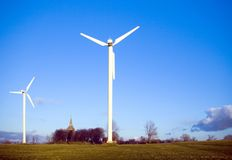 Two wind-turbines and church. Two wind-turbines, rural scenics, a small church in the background. Intensive blue sky Stock Image