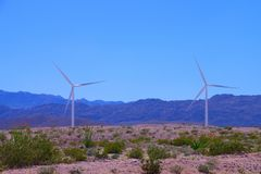 Two wind turbines in the desert in spring with mountains and clear blue sky stock images