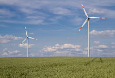 Two Wind turbines on a green field royalty free stock photo