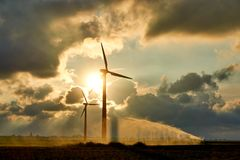 Two wind turbines and irrigating crop water gun. Or water spray at sunset in backlight against an orange colored dramatic cloudy sky and bright sun stock photography