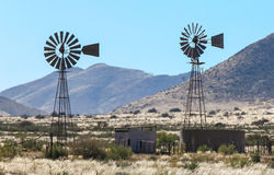 Two windmill water pumps in the heat haze on farm Royalty Free Stock Images