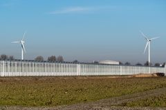 Two windmills behind a large greenhouse royalty free stock photo