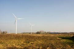 Two windmills for electric power production stock images