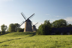 Two windmills in a field Royalty Free Stock Images