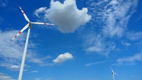 Two windmills rotating during windy summer cloudy day. With cloudy blue sky as a background stock video footage