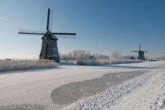 Two windmills in winter scenery Royalty Free Stock Image