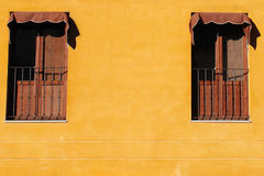 Two Windows. Two classic windows on mustard wall Stock Photos