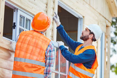 Two window fitter cooperating and installing window. For new house Stock Image