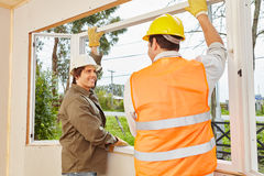 Two window fitters assemble window. In teamwork royalty free stock images