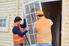 Two window fitters installing new glaziery. On woodhouse stock images