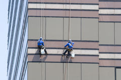 Two Window Washers. Working on the side of a high rise building Royalty Free Stock Photo